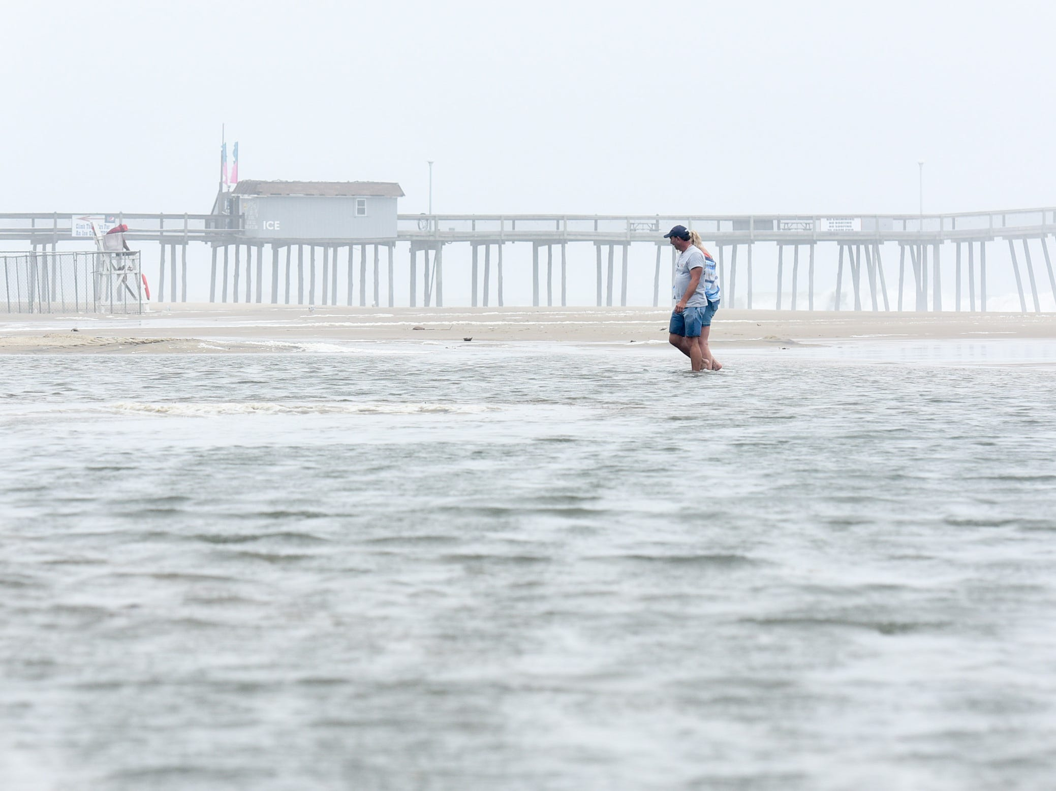 Visitors wade through flooding in front of the parking lot at Ocean City inlet on Thursday, Sept 13.