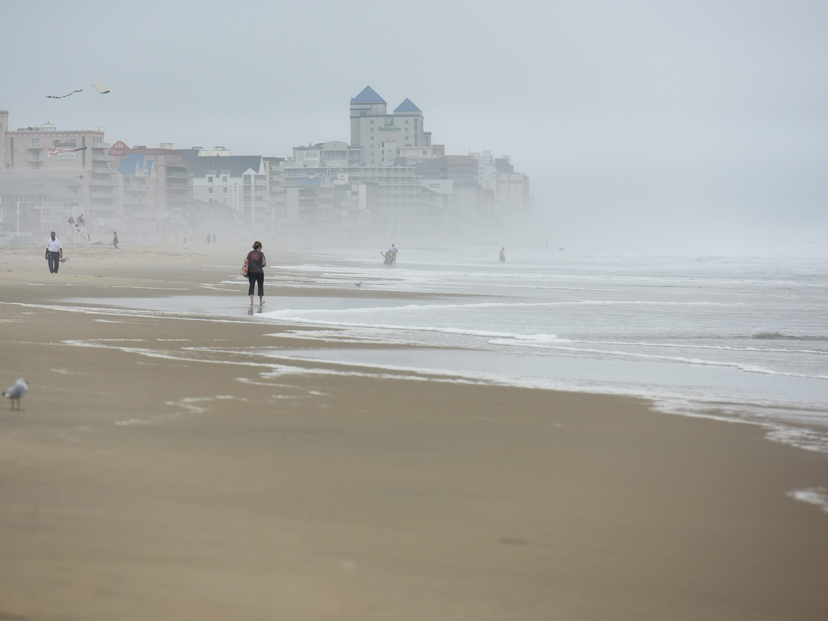 Visitors walk on the beach in Ocean City. The area saw mild flooding, wind and rough surf on Thursday, Sept 13.