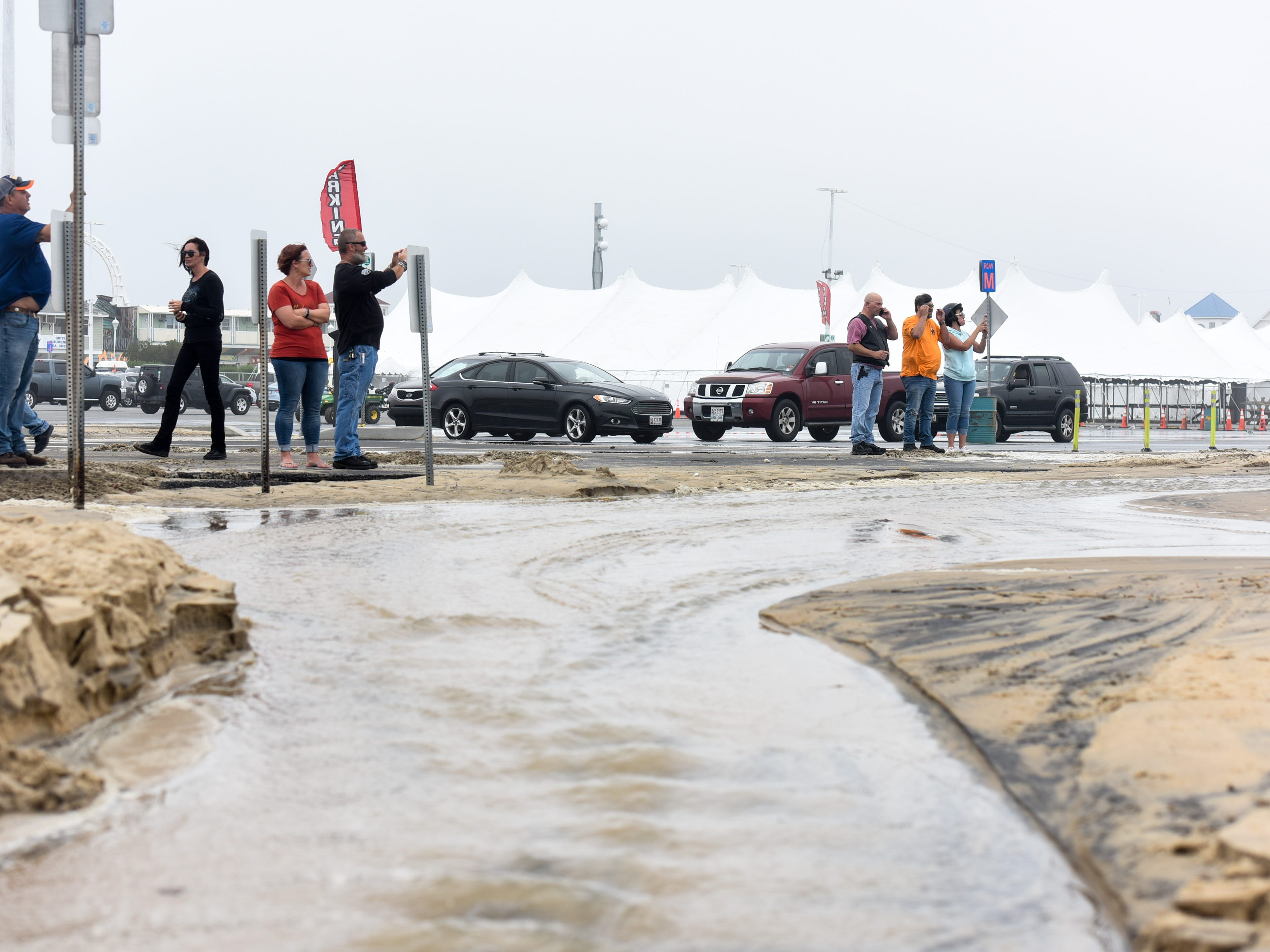 Visitors take photos at the Ocean City inlet. The area experienced mild flooding, wind and rough surf on Thursday, Sept 13.