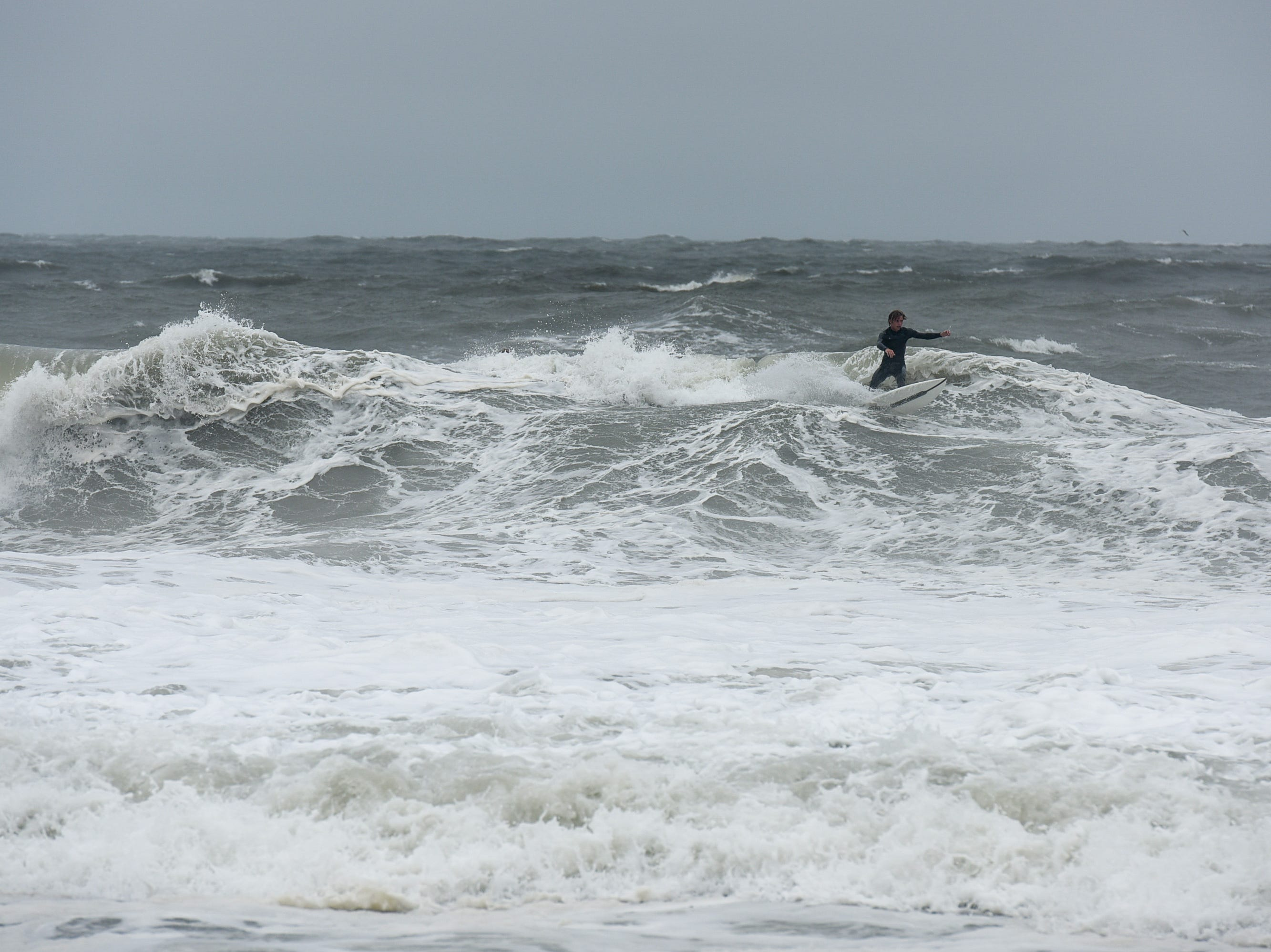 A surfer catches a wave at the Ocean City inlet. The area experienced mild flooding, wind and rough surf on Thursday, Sept 13.