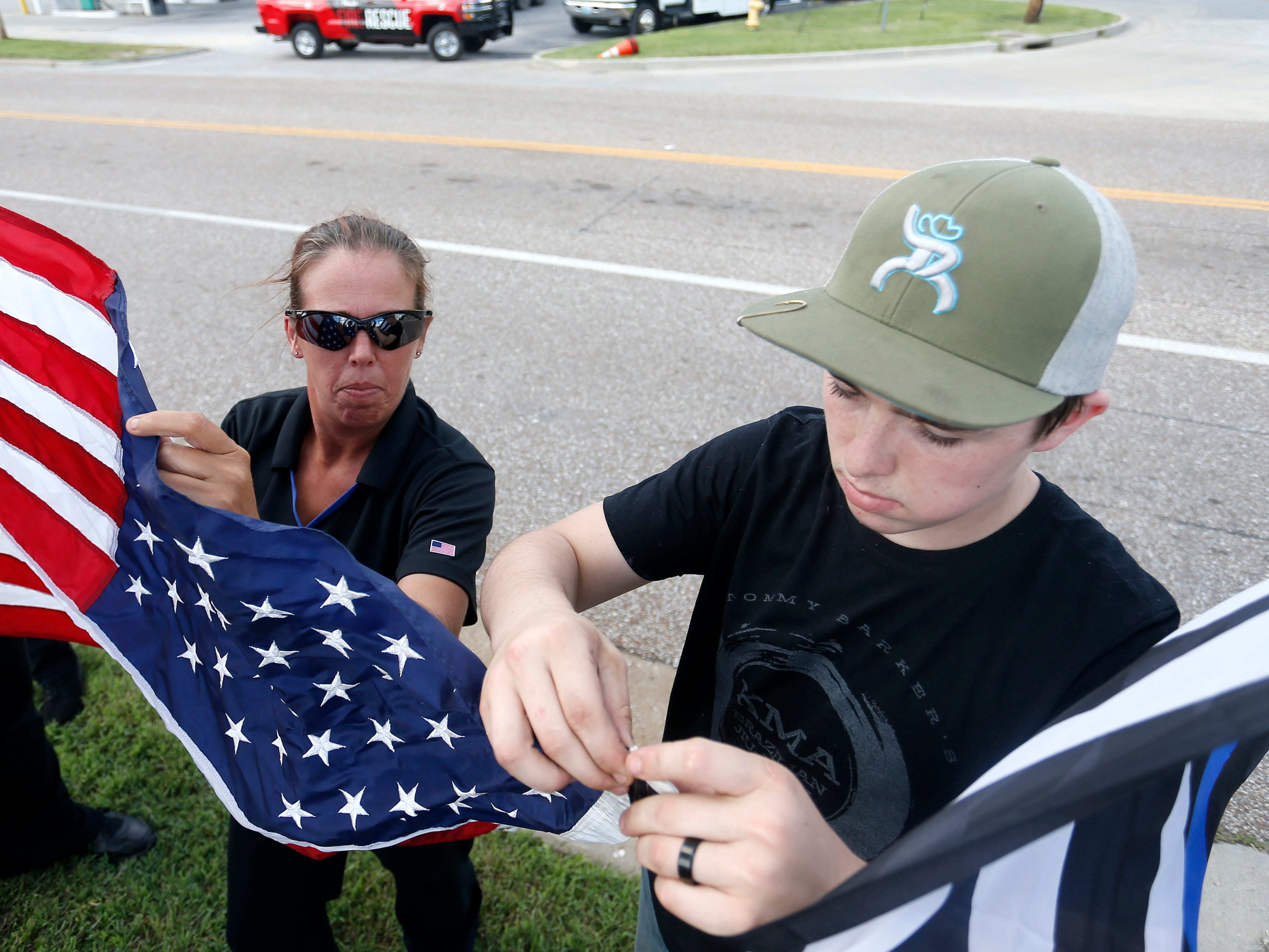 Police supporters Kirsten and Trevor Van Nest, 16, hang an American Flag and a thing blue line flag for the funeral procession for Deputy Aaron Roberts on Thursday, Sep. 13, 2018.