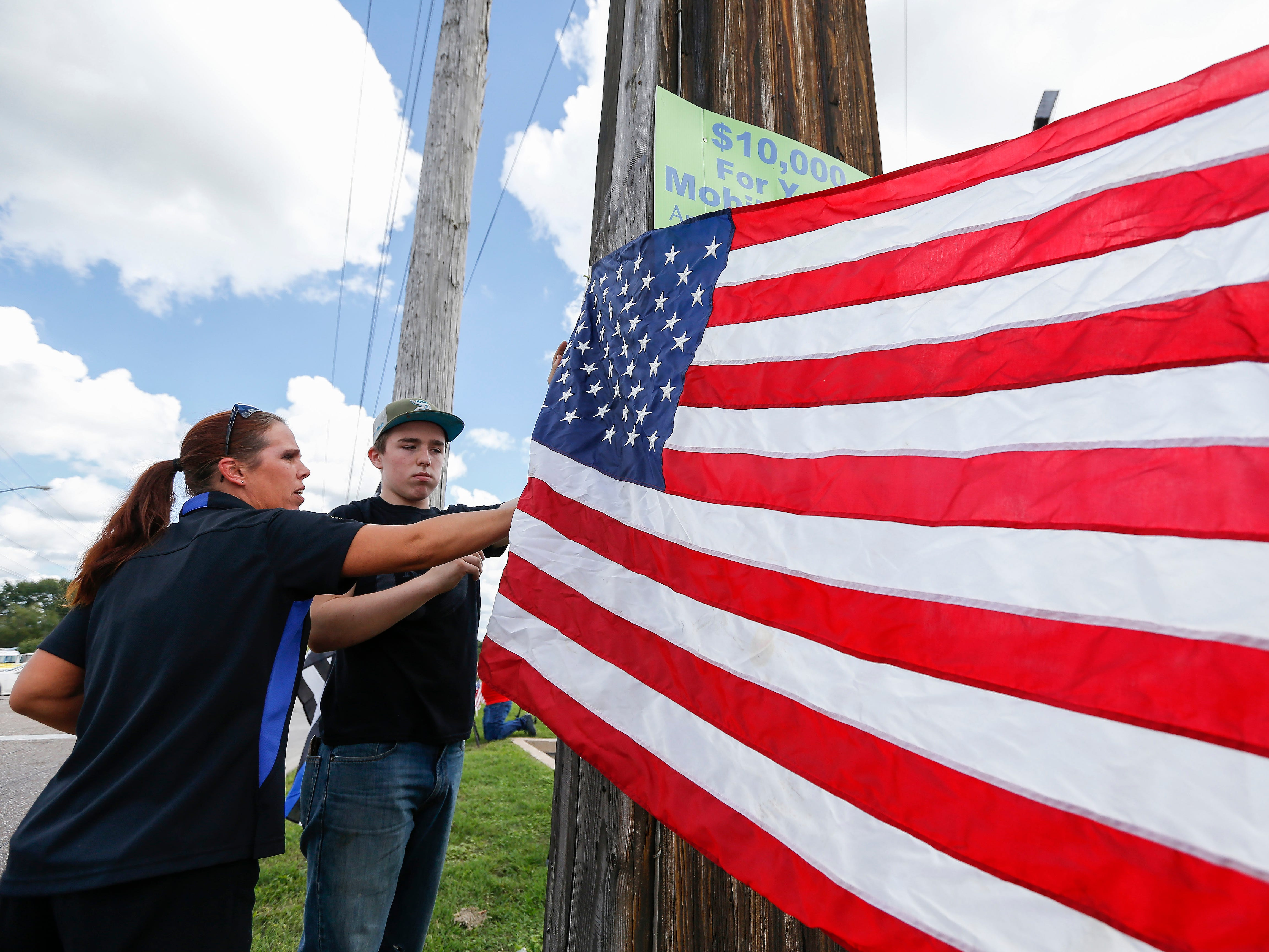 Kirsten Van Nest and her son Trevor Van Nest hang up a flag near the intersection of Glenstone Avenue and McClernon Street before the funeral procession for Deputy Aaron Roberts.