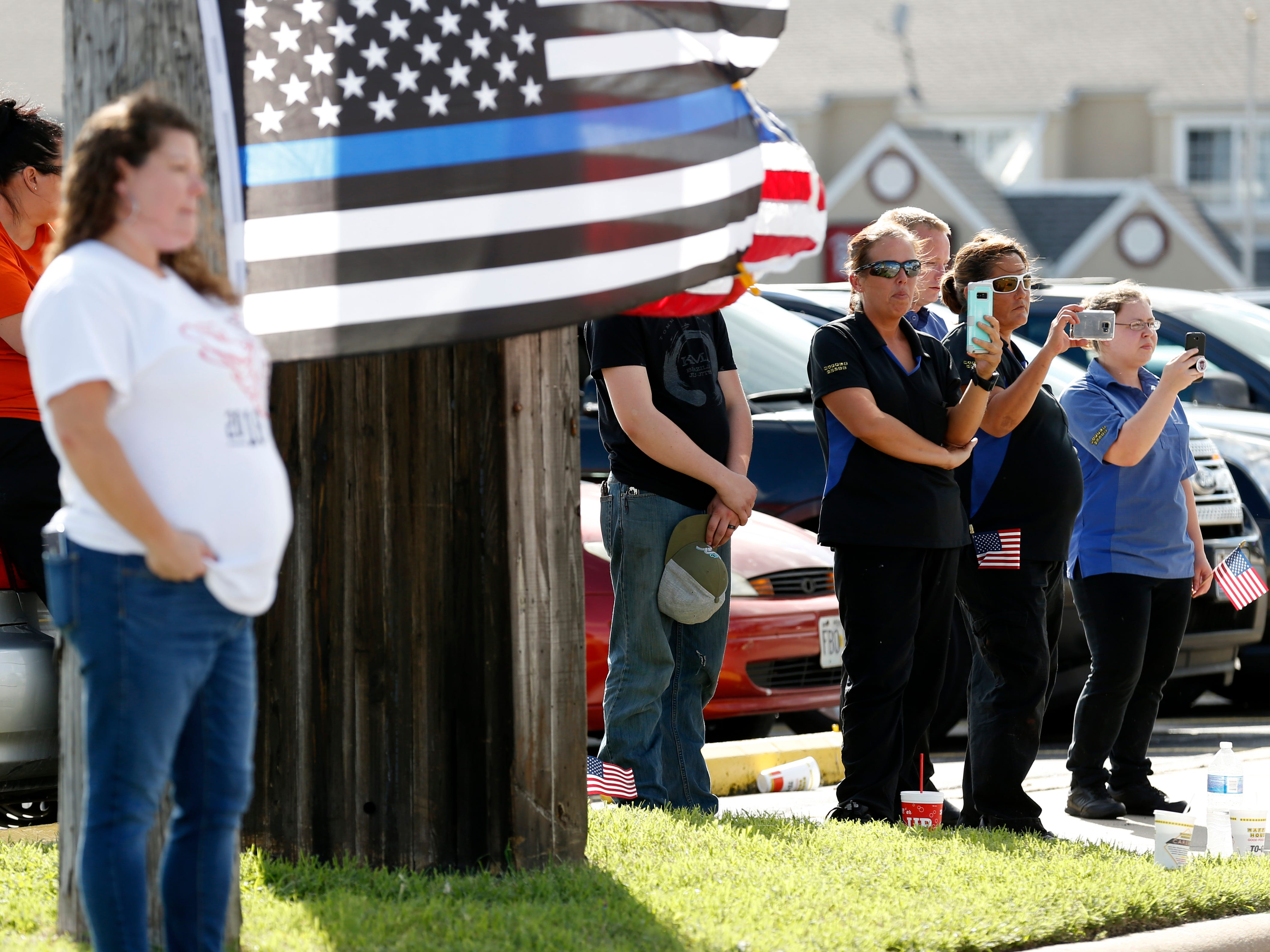 Supporters watch the funeral procession for Deputy Aaron Roberts as it passes by on Thursday, Sep. 13, 2018.