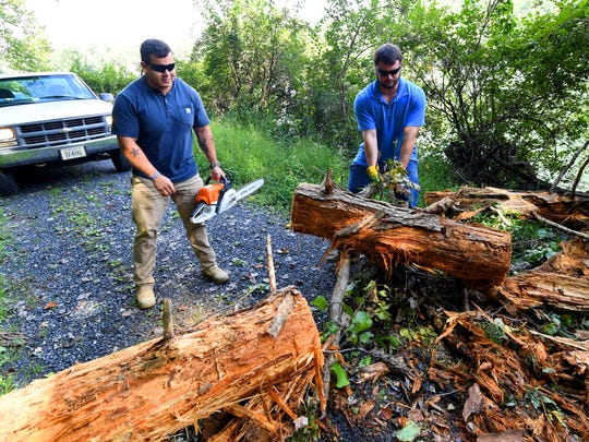 Michael Jimenez, a dam technician with Headwaters Soil and Water Conservation District, has the chainsaw as conservation technician Aaron Lucas pulls part of a downed tree clear of the road. The pair try to reach the dam at Elkhorn Lake to check the location's Integrated Flood Observing and Warning Systems (aka. IFLOWS) gauge on Thursday, Sept. 13, 2018.