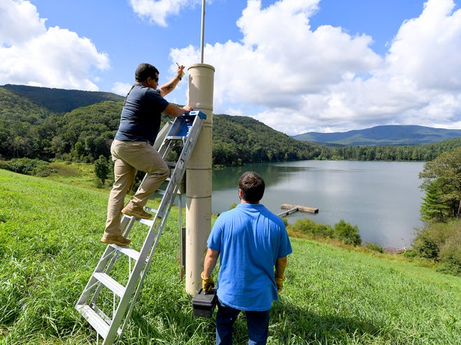 Michael Jimenez, a dam technician with Headwaters Soil and Water Conservation District, stands on a ladder with conservation technician Aaron Lucas below. The pair check the Integrated Flood Observing and Warning Systems (aka. IFLOWS) gauge at the dam at Elkhorn Lake on Thursday, Sept. 13, 2018.