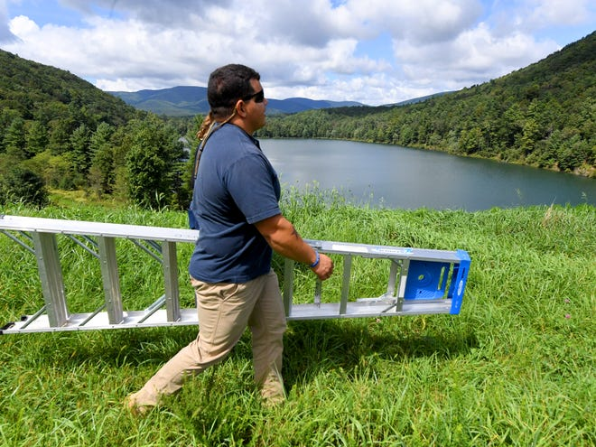 Michael Jimenez, a dam technician with Headwaters Soil and Water Conservation District, carries the ladder. Jimenez and conservation technician Aaron Lucas visit the dam at Elkhorn Lake to check the location's Integrated Flood Observing and Warning Systems (aka. IFLOWS) gauge on Thursday, Sept. 13, 2018.