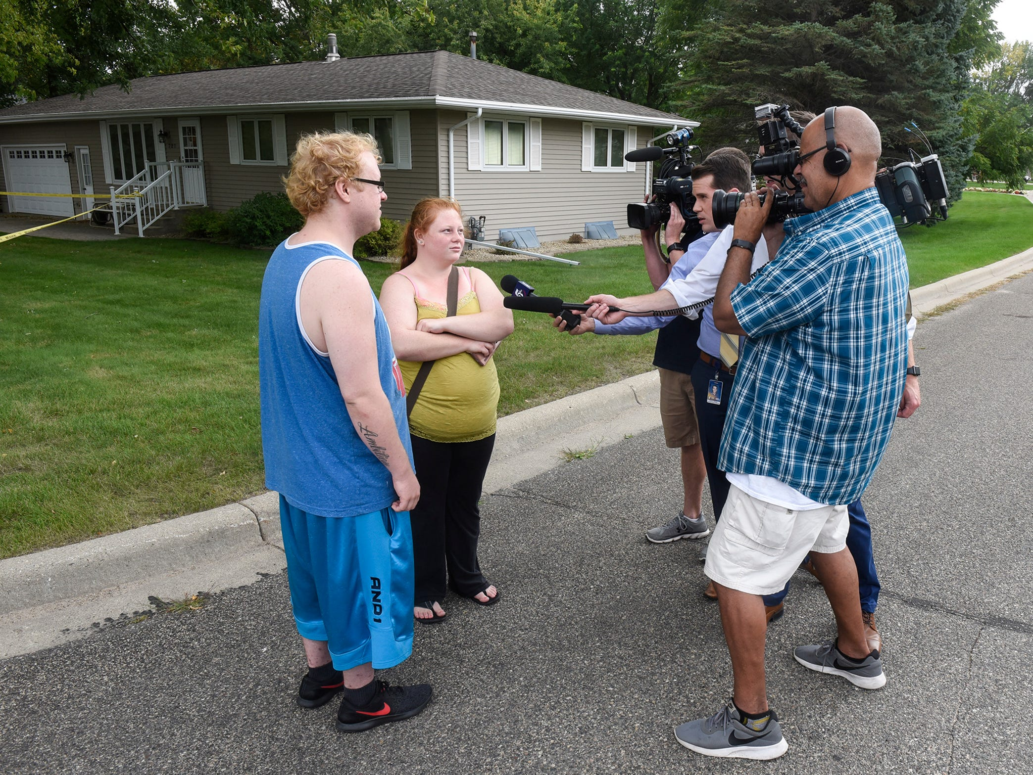 Brandon Schindler and Katelynn Cheadle answer questions from television reporters near the scene where a Stearns County deputy was shot with an arrow Thursday, Sept. 13, in Sauk Centre.