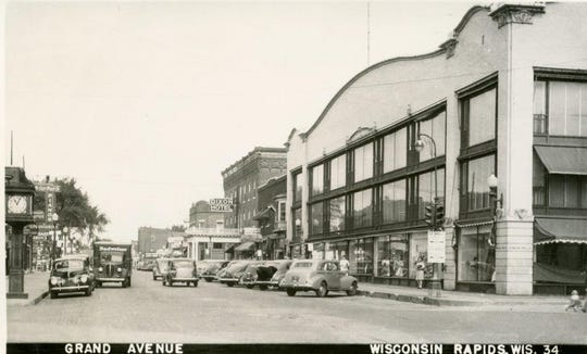 This photograph faces west along West Grand Avenue. The Dixon Hotel stands west of Johnson & Hill Department Store. A piano shop and service stores are across the street.