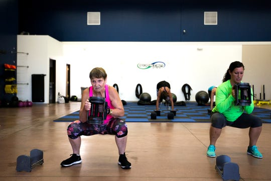 Betty Lou Sweeney, left, does squats with a weight during an interval training workout at Forever Fit in Plover, Wis., September 12, 2018.