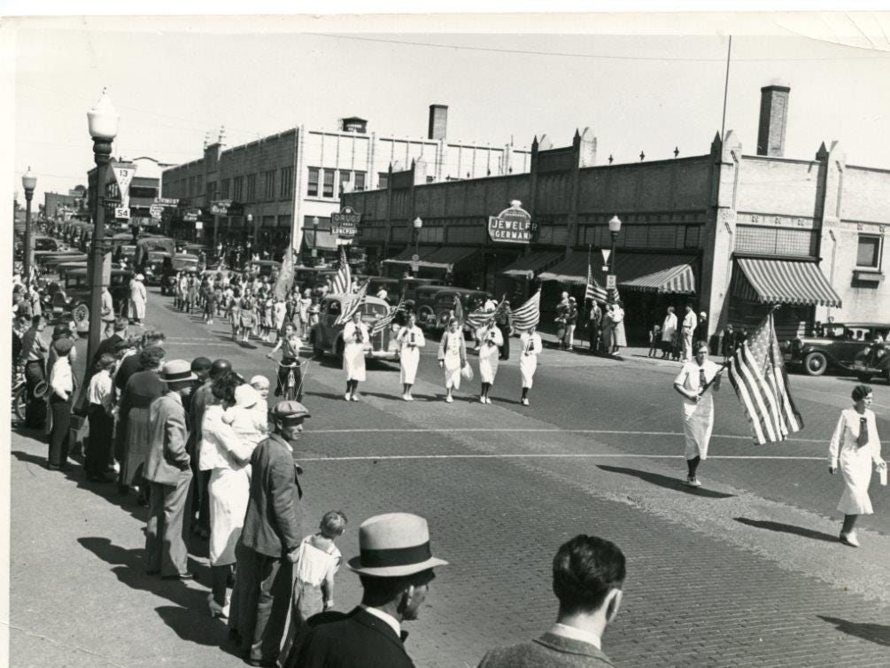 A photo of a parade shows the Johnson & Hill Department Store, the Mead-Witter Block and the River Block, featuring sotres like Germann's Jewelry, a restaurant and drug store.