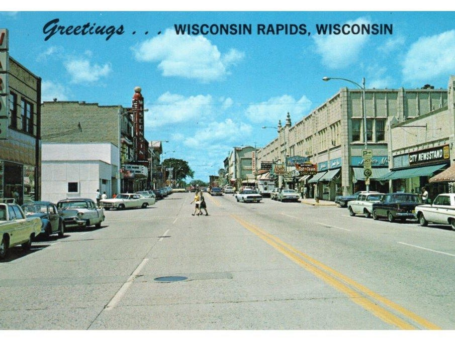 A postcard shows the western view along West Grand Avenue. City Newsstand is at the end of the River Block, stores like Tot n Teen Toyland, Wilpolt's Restaurant and clothing stores serve customers on the Mead-Witter Block. The Wisconsin Theater sign stands above the Theater Block.