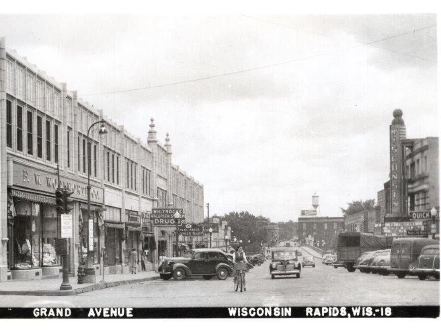 West Grand Avenue, facing east shows F. W. Woolworth Co., Whitrock's Drug Store, Frank Abel's Clothes Shop and Wilpolt's Restaurant on the Mead-Witter Block.