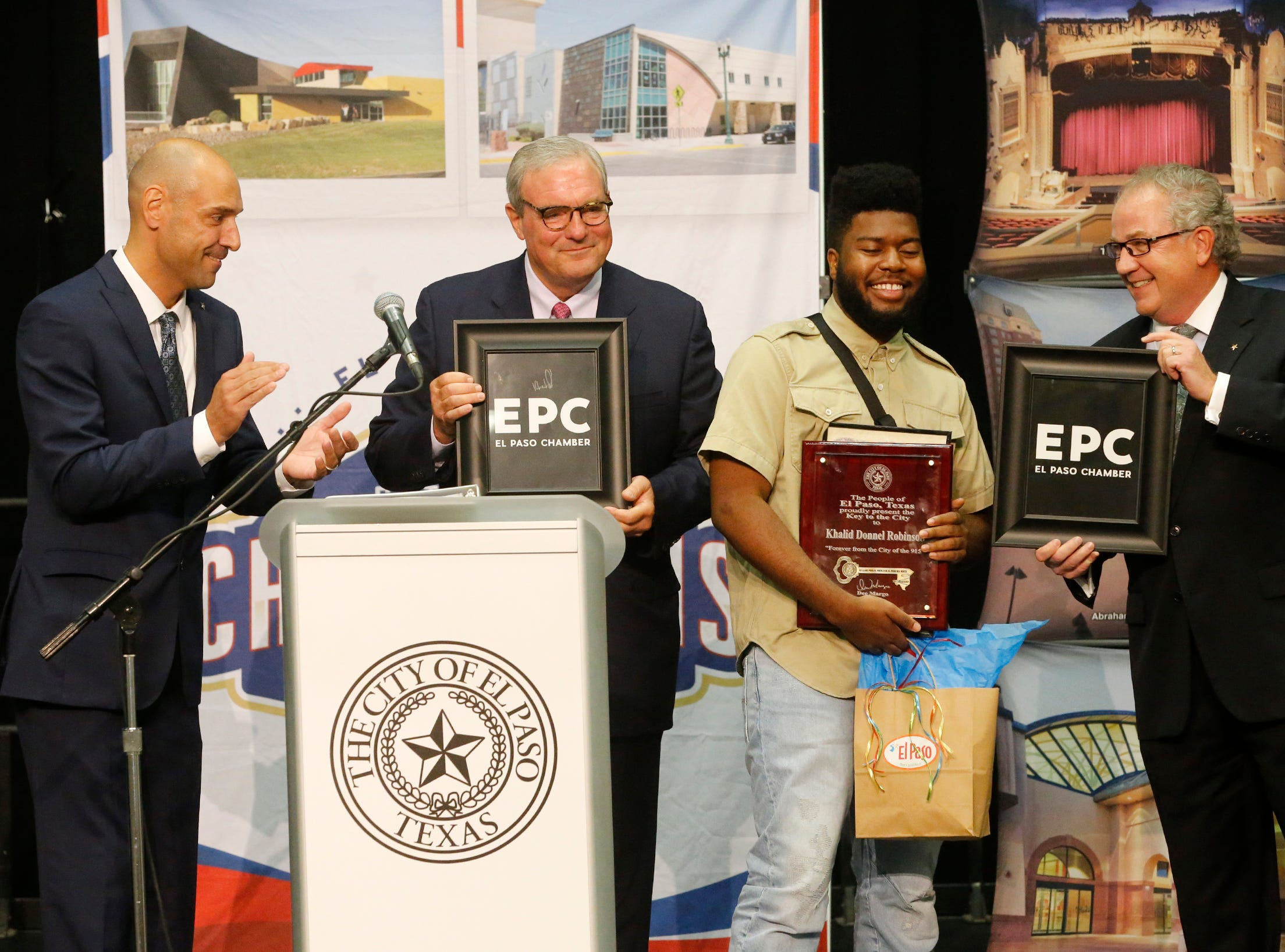 Recording artist and El Pasoan Khalid along with El Paso Mayor Dee Margo (second from left) and ElPaso Chamber President and CEO David M. Jerome gives Khalid some gifts from the chamber shortly after Mayor Margo presented Khalid with the Key to the City after delivering his first State of the City address.