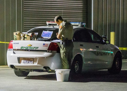 A Kern County sheriff's deputy works at the scene of Wednesday's fatal rampage in Bakersfield. A gunman killed his wife, four others and himself, authorities said.