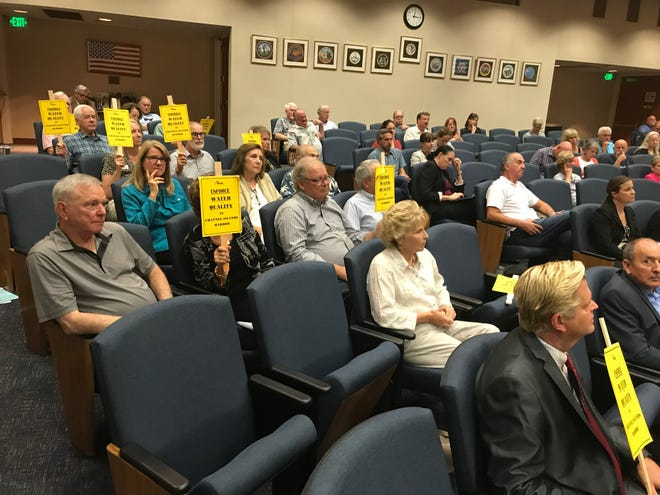 "Channel Islands Harbor residents hold up signs that read ""Please enforce water quality in Channel Islands Harber"" during a Thursday meeting of the Los Angeles Regional Water Quality Control Board."