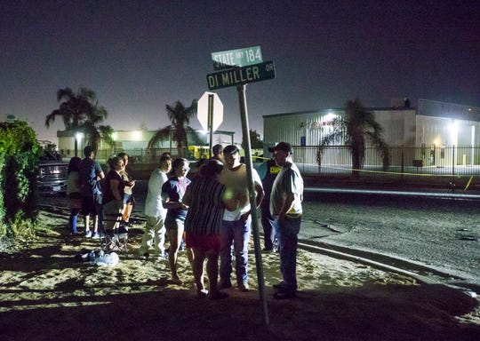A crowd gathers near a location where a gunman opened fire, killing several people, Wednesday in Bakersfield.
