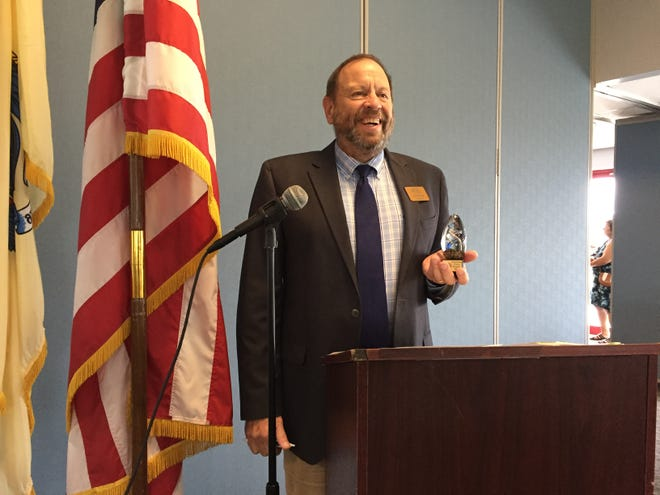 Larry Malone, president of the Greater Millville Chamber of Commerce, holds one of the awards distributed Wednesday to past Outstanding Citizen award recipients. The awards luncheon was held at New Jersey Motorsports Park.