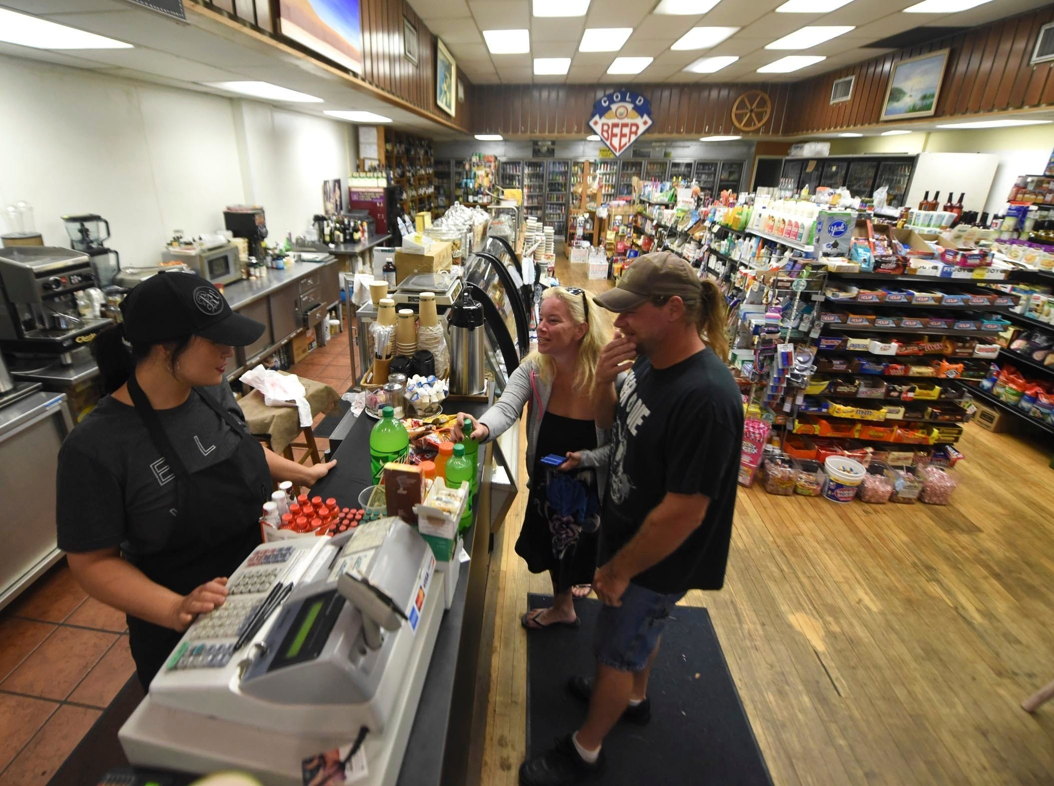 Donna Stamm, left, manager of Gourmet Market, checks out customers at the store in downtown Wilmington, N.C., ahead of Hurricane Florence, Thursday, Sept.  13, 2018. Stamm lives downtown and was planning on staying open as long as possible.  (Matt Born/The Star-News via AP)