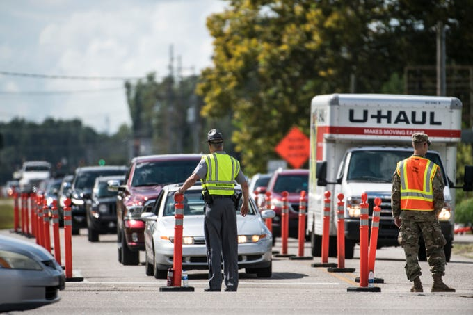 Members of law enforcement work with the National Guard to direct traffic onto U.S. Highway 501 as Hurricane Florence approaches the East Coast Wednesday, Sept. 12, 2018, near Conway, S.C. Time is running short to get out of the way of Hurricane Florence, a monster of a storm that has a region of more than 10 million people in its potentially devastating sights. (AP Photo/Sean Rayford)