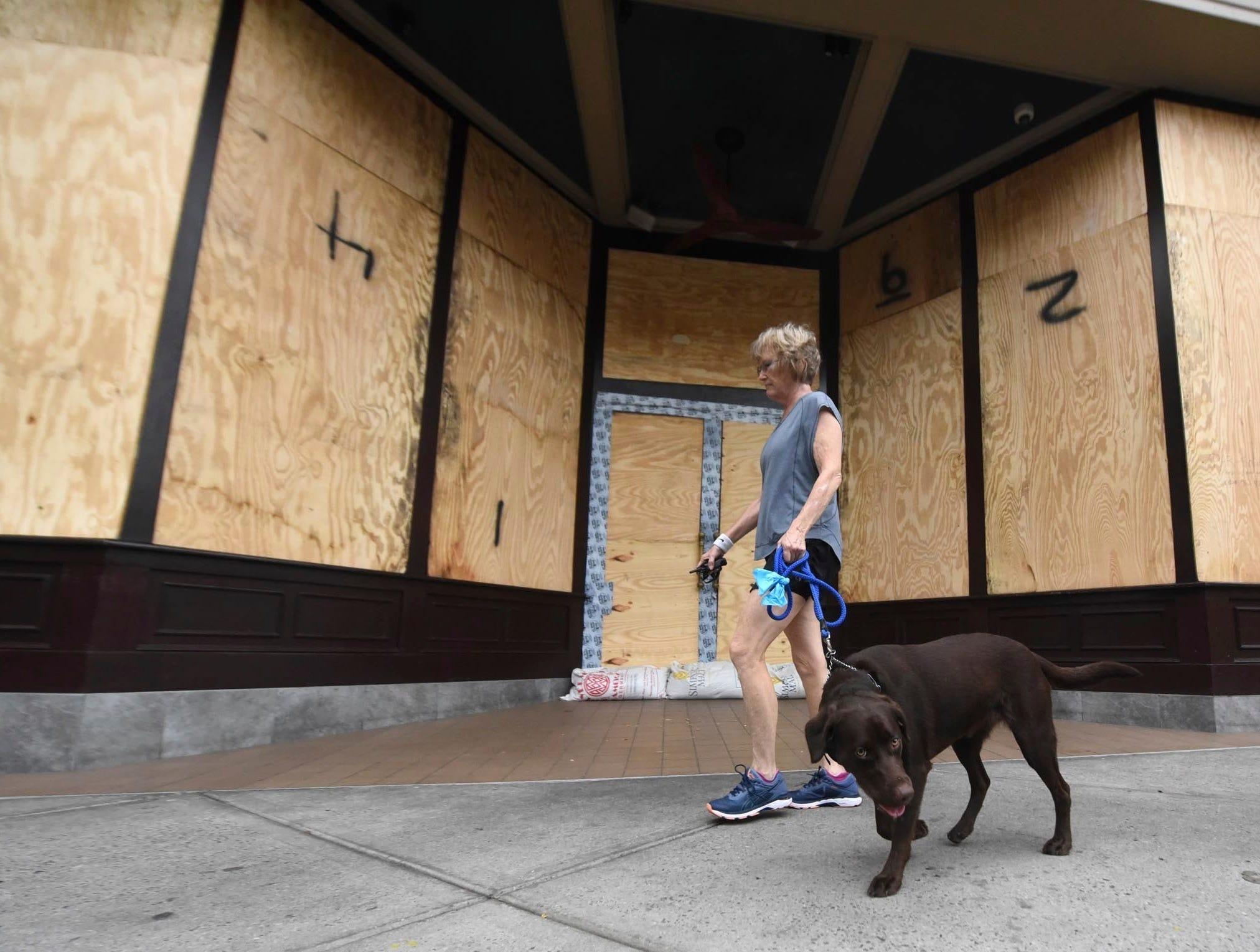 Deborah Covington walks his dog past Front Street Brewery in downtown Wilmington, N.C., Thursday, Sept. 13, 2018 ahead of Hurricane Florence.  (Matt Born/The Star-News via AP)