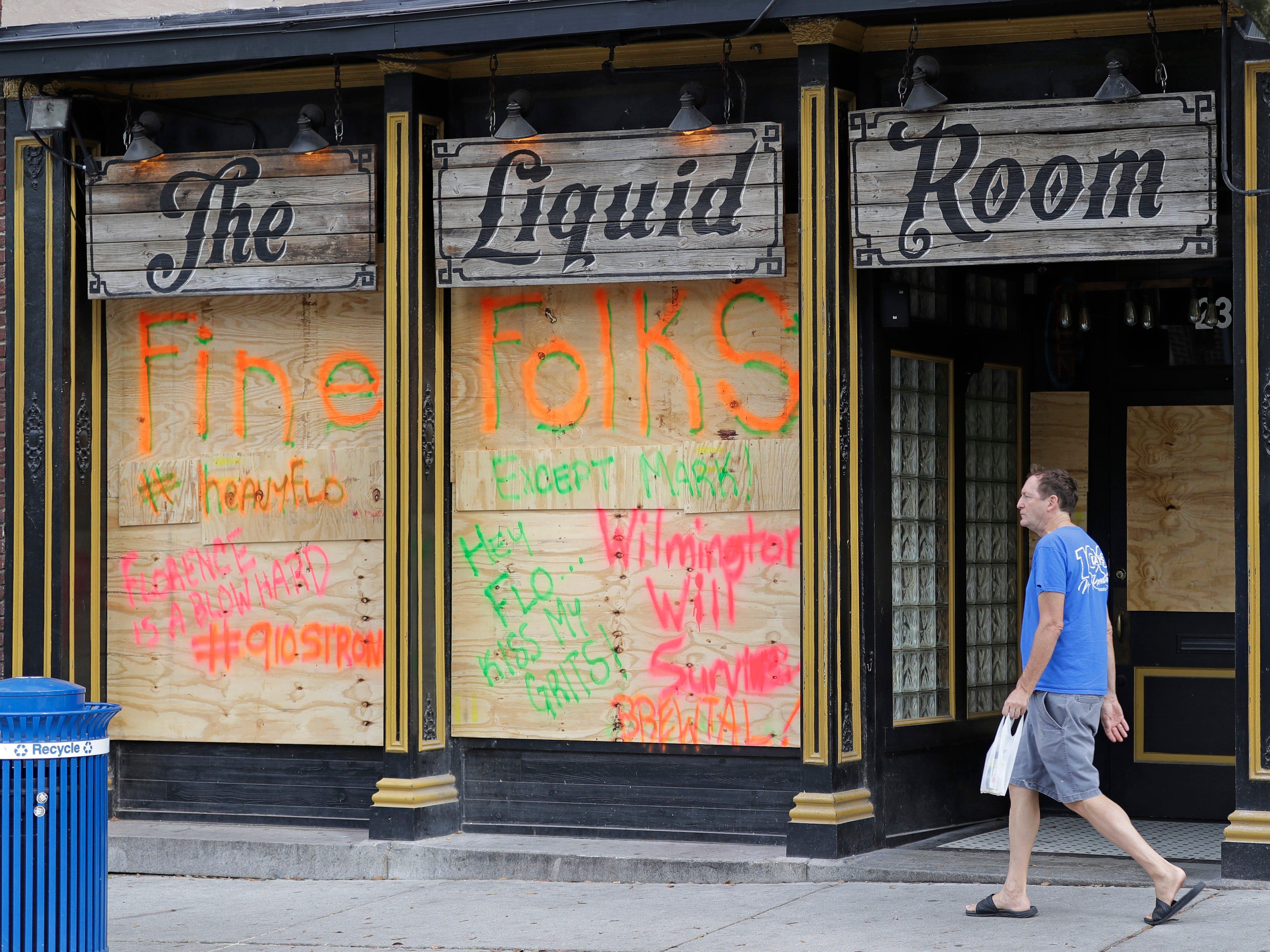A man walks past a closed bar in downtown Wilmington, N.C., as Hurricane Florence threatens the coast Thursday, Sept. 13, 2018. (AP Photo/Chuck Burton)