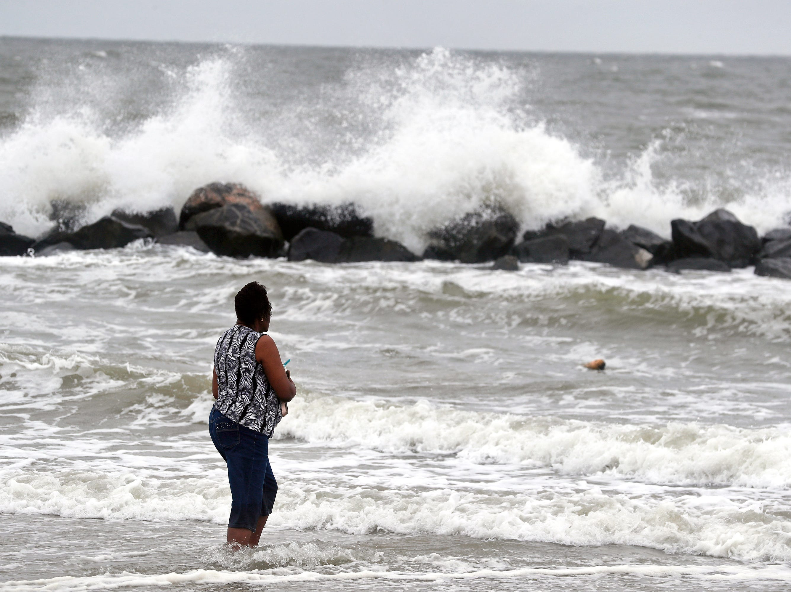 Gwen Patterson watches as waves crash ashore at Buckroe Beach in Hampton, Va., Thursday, Sept. 13, 2018 as Hurricane Florence approaches the coast.  (Jonathon Gruenke/The Daily Press via AP)