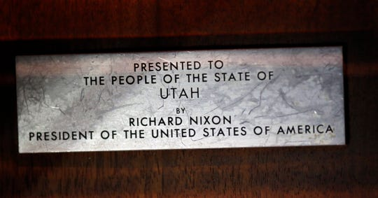 This 2018 photo shows a plate mounted on a wooden plaque that holds moon rocks encased in acrylic at the Clark Planetarium, in Salt Lake City.