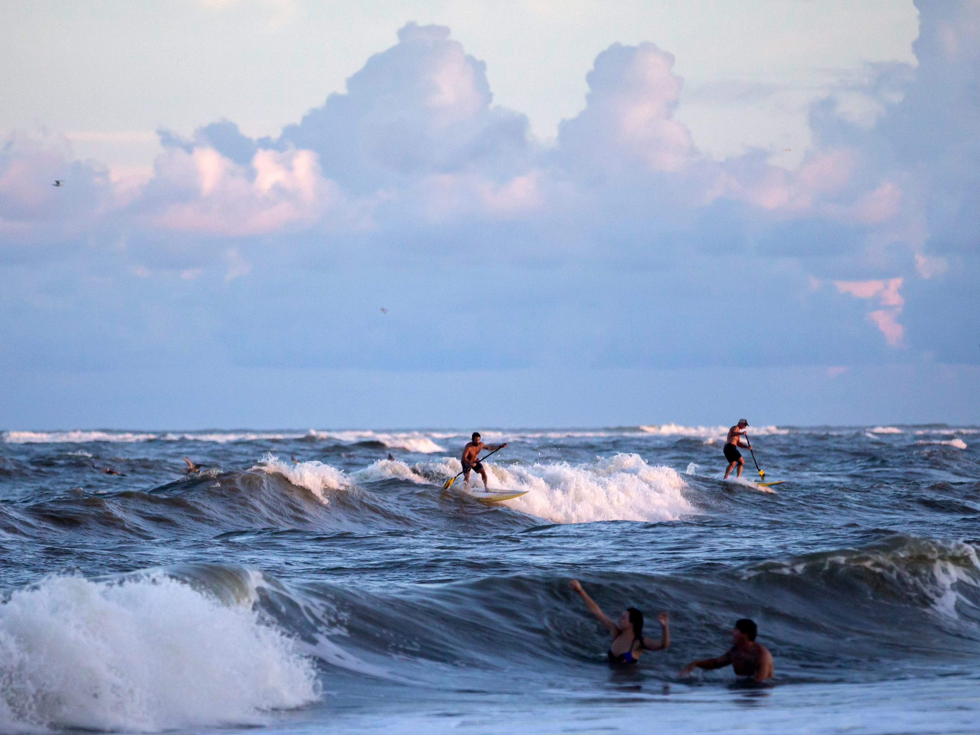 Stand-up paddle surfer Travis Storey, center, rides a wave from the approaching Hurricane Florence, Wednesday, Sept., 12, 2018, on the south beach of Tybee Island, Ga. Storey said the waves have been gradually building in size as the storm draws closer to the East Coast. (AP Photo/Stephen B. Morton)