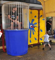 Fit Body Boot Camp owner Joe Harris watches as Crew Edwards, 4, attempts to dunk him in a dunking tank for the Texoma Gives fundraiser Thursday morning at Frank & Joe's Coffee House. Frank & Joe's co-founder Jessica Edwards said they are helping to raise money for the Child Advocates of Red River.