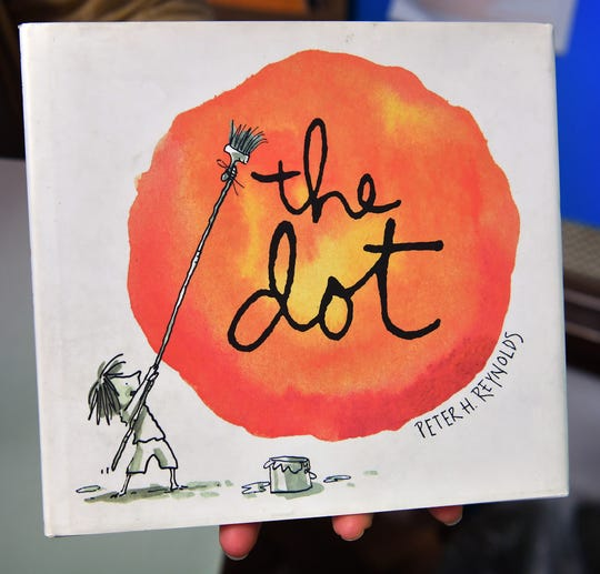 The childrens book, The Dot, by Peter Reynolds, the story of a little girl, Vashti, who thinks she can't make art but is encouraged by her teacher to just start with a dot and ends up making her mark on the world.