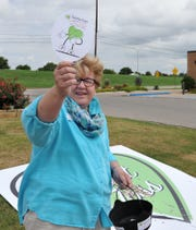 Texoma Gives volunteer Kathy Kabell, supervisory manager at WMH Group, flags down motorists for donations, Thursday morning during the Texoma Gives event. WMH Group is raising money for all area volunteer fire departments.