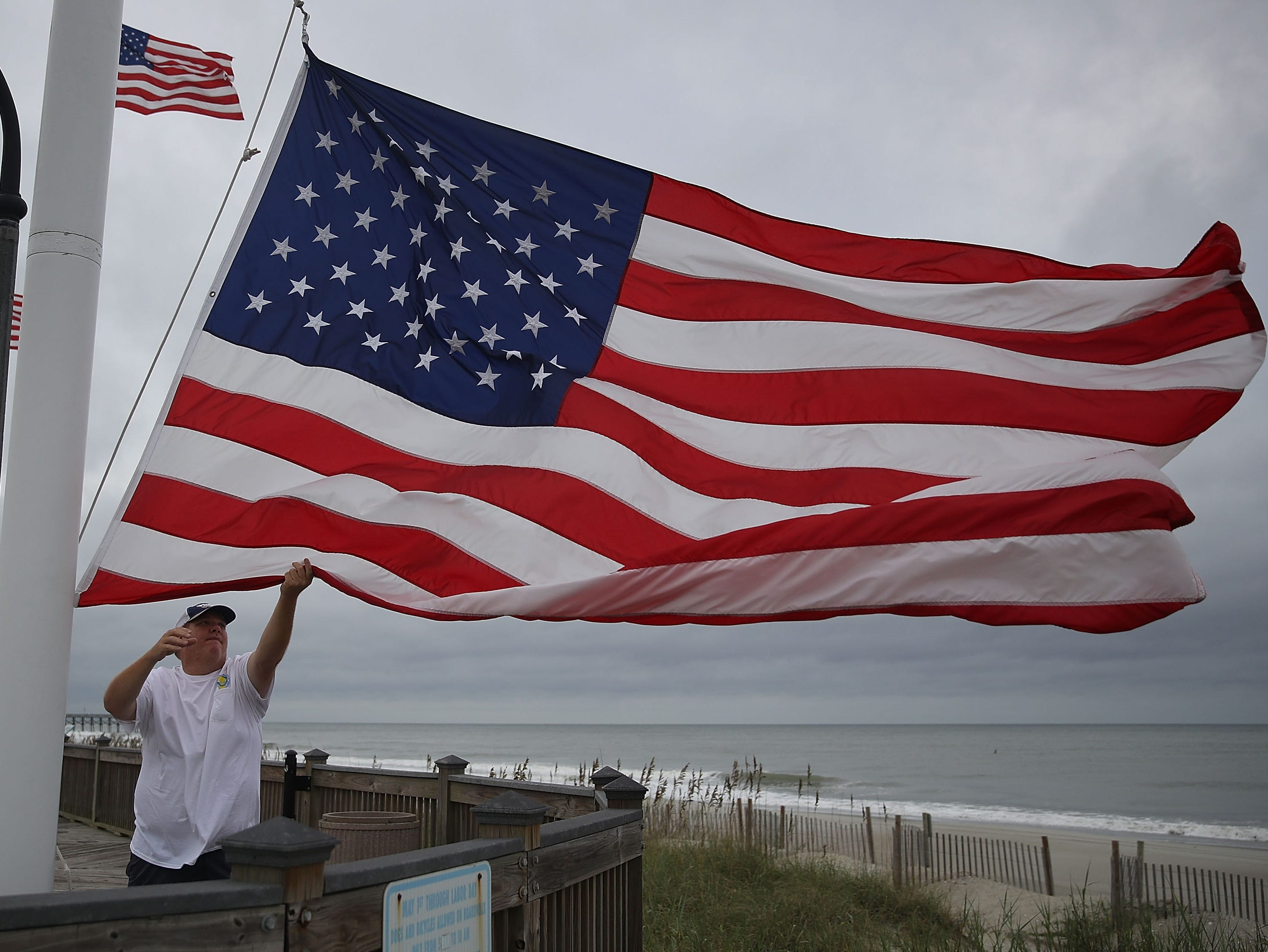 Jason Morris takes down one of several American flags ahead of the arrival of Hurricane Florence on Sept. 13, 2018 in Myrtle Beach, United States. Hurricane Florence is expected to arrive on Friday possibly as a category 2 storm along the North Carolina and South Carolina coastline.