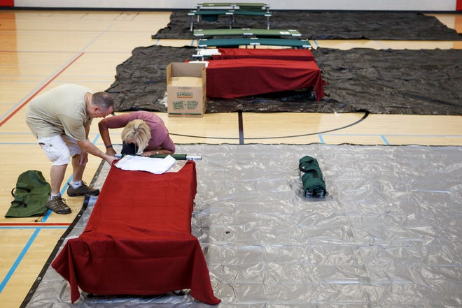 Volunteer Chuck Cruthirds, left, and April Martin, with American Red Cross Disaster Cycle Services, help set up a cot in the gym at the Brainerd Youth and Family Development Center on Thursday, Sept. 13, 2018 in Chattanooga, Tenn. The Hamilton County Office of Emergency Management, American Red Cross and other organizations are joining to open and operate a shelter at the Brainerd Youth & Family Development Center for coastal residents fleeing Hurricane Florence, according to a news release.