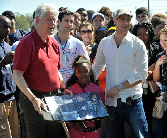 President Bill Clinton and Brad Pitt,founder of the Make It Right foundation, pose with DeeCarla Rogers while they greet volunteers and break ground for new homes in the Lower Ninth Ward, New Orleans, March 16, 2008.