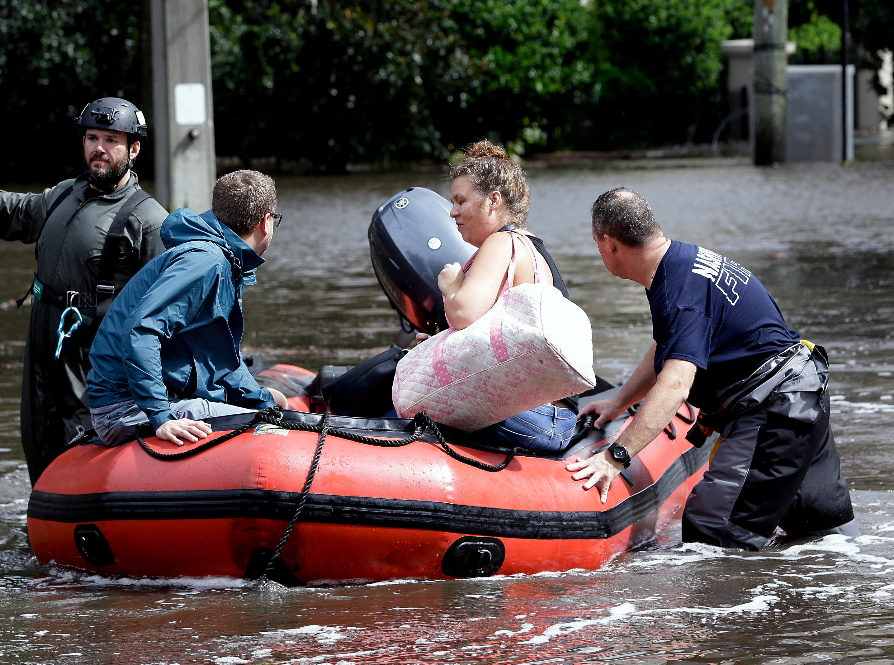 Rescue workers help a couple evacuate their home that was flooded after Hurricane Irma in Jacksonville, Fla.