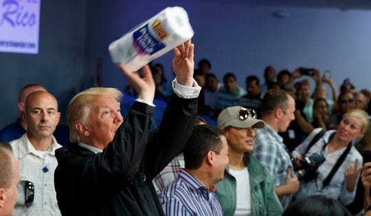President Donald Trump tosses paper towels into a crowd at Calvary Chapel in Guaynabo, Puerto Rico on Oct. 3, 2017.