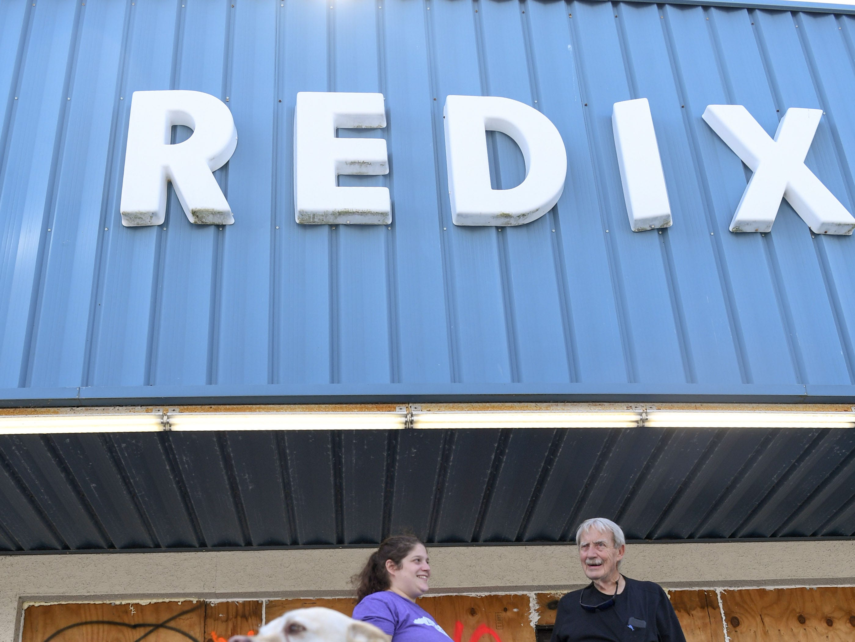 Waylon the dog, left, Meredith Reddick, middle, and her father Gordon owner of Redix store, stand with plywood covered windows Sept.  11, 2018. They have used the same boards since 1993, and wrote names for each storm since then.