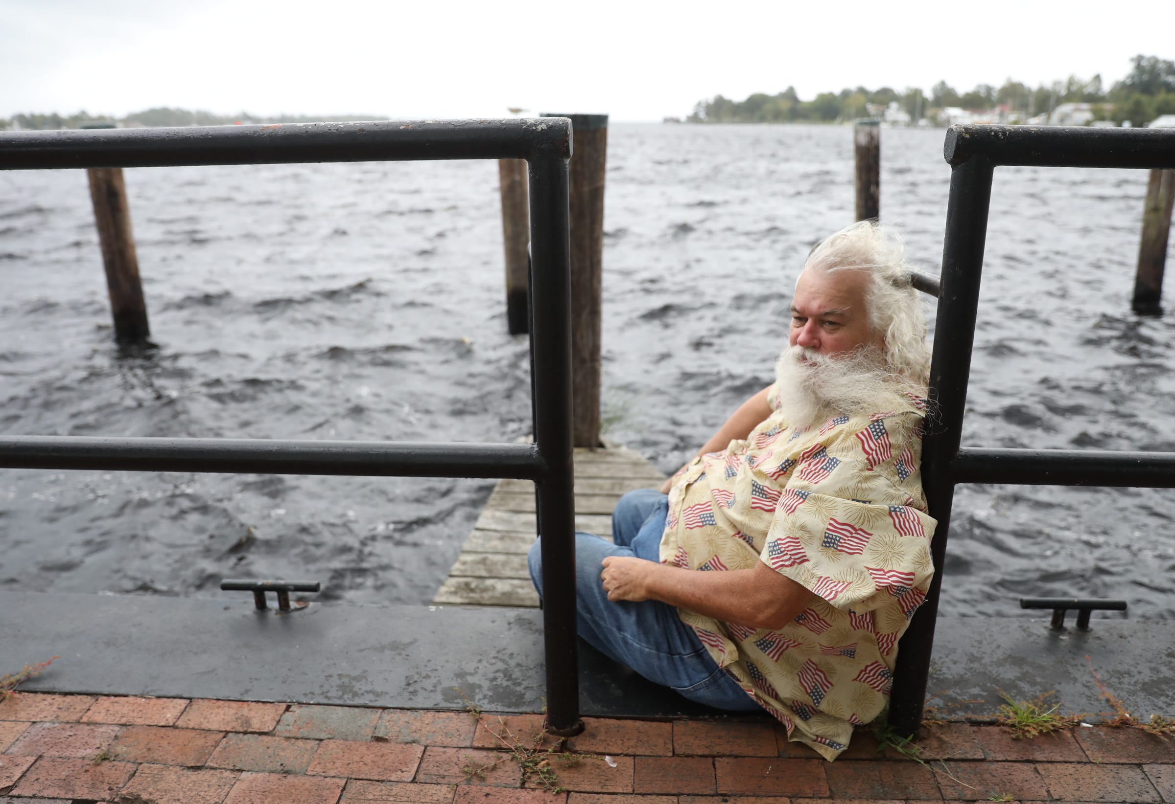 Daniel Harris sits on the bulkhead of Mariners' Wharf Park in downtown Elizabeth City, N.C., on Sept. 13, 2018. Harris plans to ride out the storm in his home.