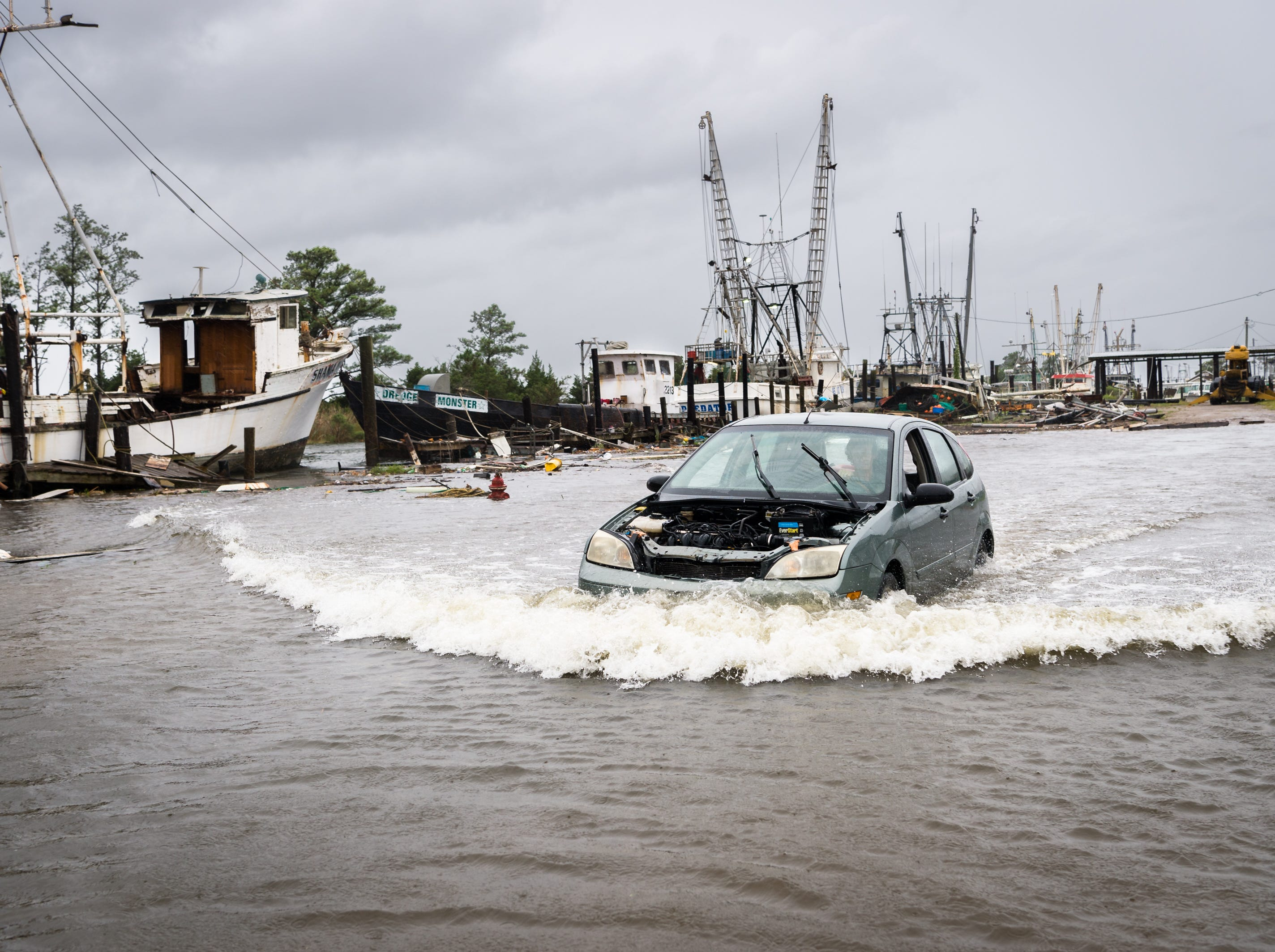 A motorist drives through a flooded area in the Swan Quarter harbor in Swan Quarter, N.C as Hurricane Florence makes landfall Sept. 13, 2018.