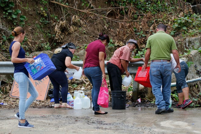 People gather water in the town of Comerio which is without potable water due to the impact on infrastructure of Hurricane Maria in Puerto Rico on Sept. 30, 2017.