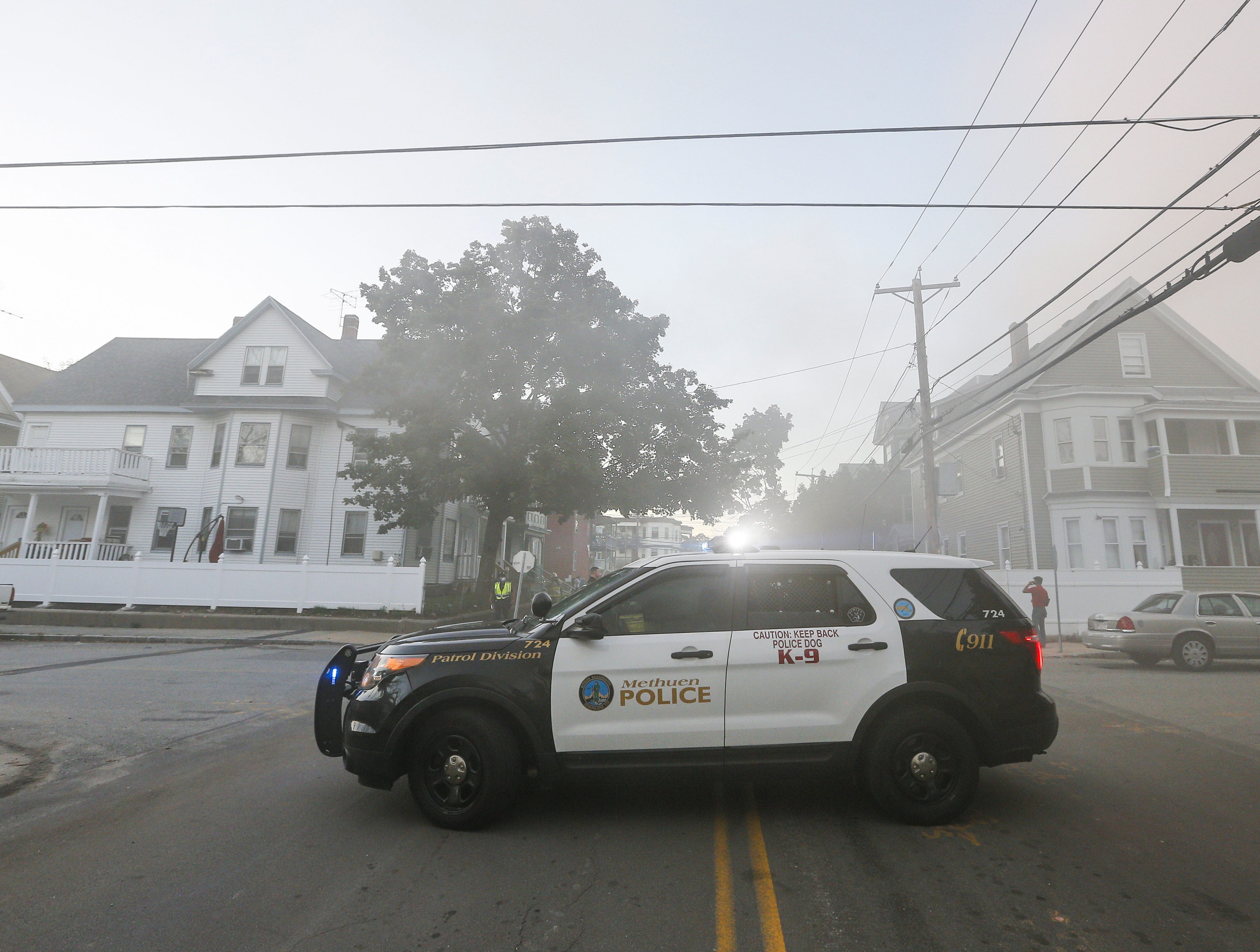 A police car blocks a road in a smoke filled neighborhood as firefighters battle house fires in Lawrence, Mass., Sept. 13, 2018.
