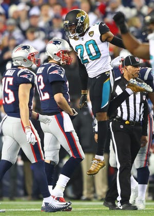 New England Patriots quarterback Tom Brady (12) walks off the field as Jacksonville Jaguars cornerback Jalen Ramsey (20) celebrates a play during the AFC Championship at Gillette Stadium.