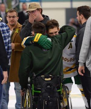 Returning Humboldt Broncos player Brayden Camrud (26) hugs former teammate Jacob Wassermann during a pregame ceremony.