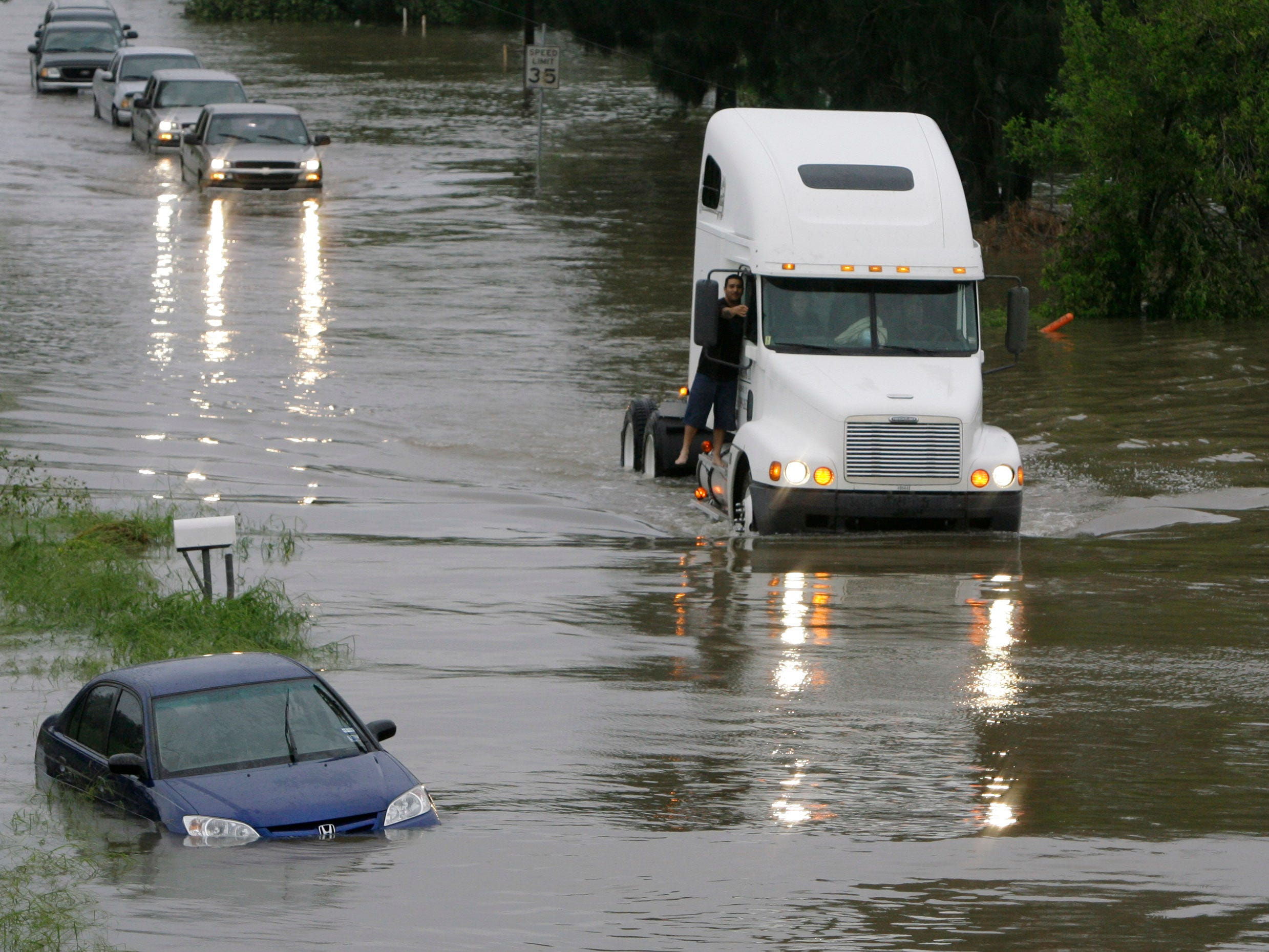 A truck leads a pack of cars down a flooded street after Hurricane Dolly, Thursday, July 24, 2008, in Harlingen, Texas.
