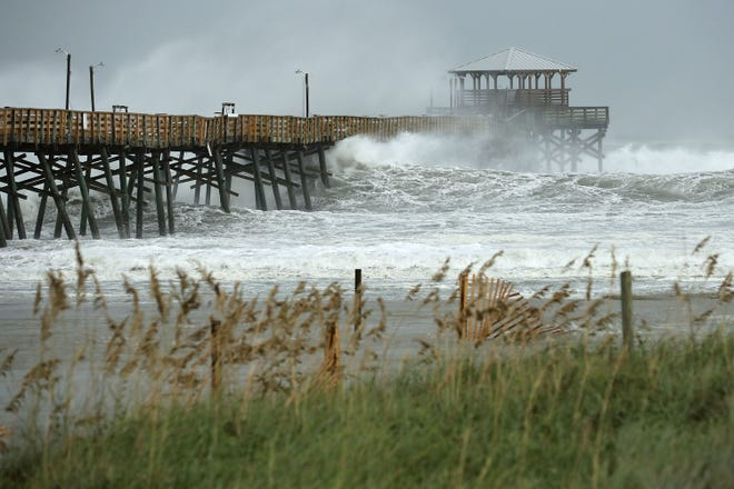 Waves crash around the Oceana Pier as the outer edges of Hurricane Florence being to affect the coast September 13, 2018 in Atlantic Beach.