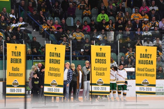 Humboldt Broncos current and former players look on from the background as banners are unveiled during a tribute.