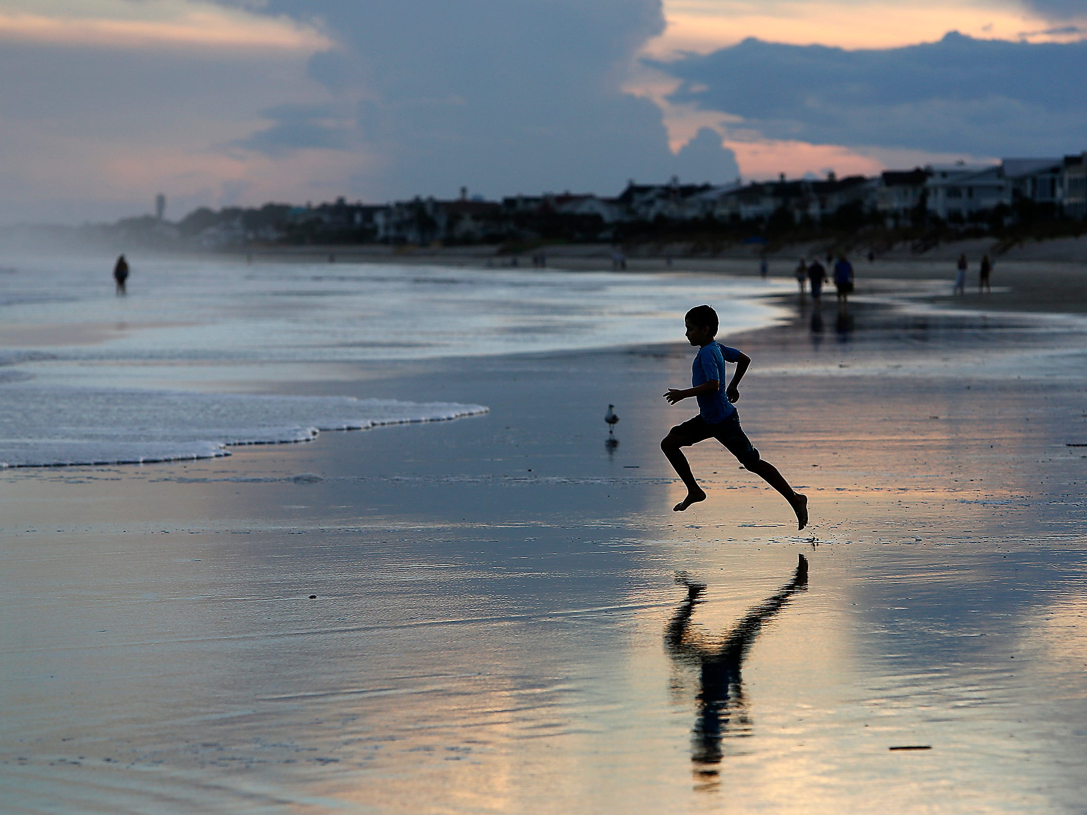 A boy runs to the ocean at sunset on the Isle of Palms, S.C., as Hurricane Florence slightly weakens but remains a potentially catastrophic storm in the Atlantic ocean on Sept. 12, 2018.