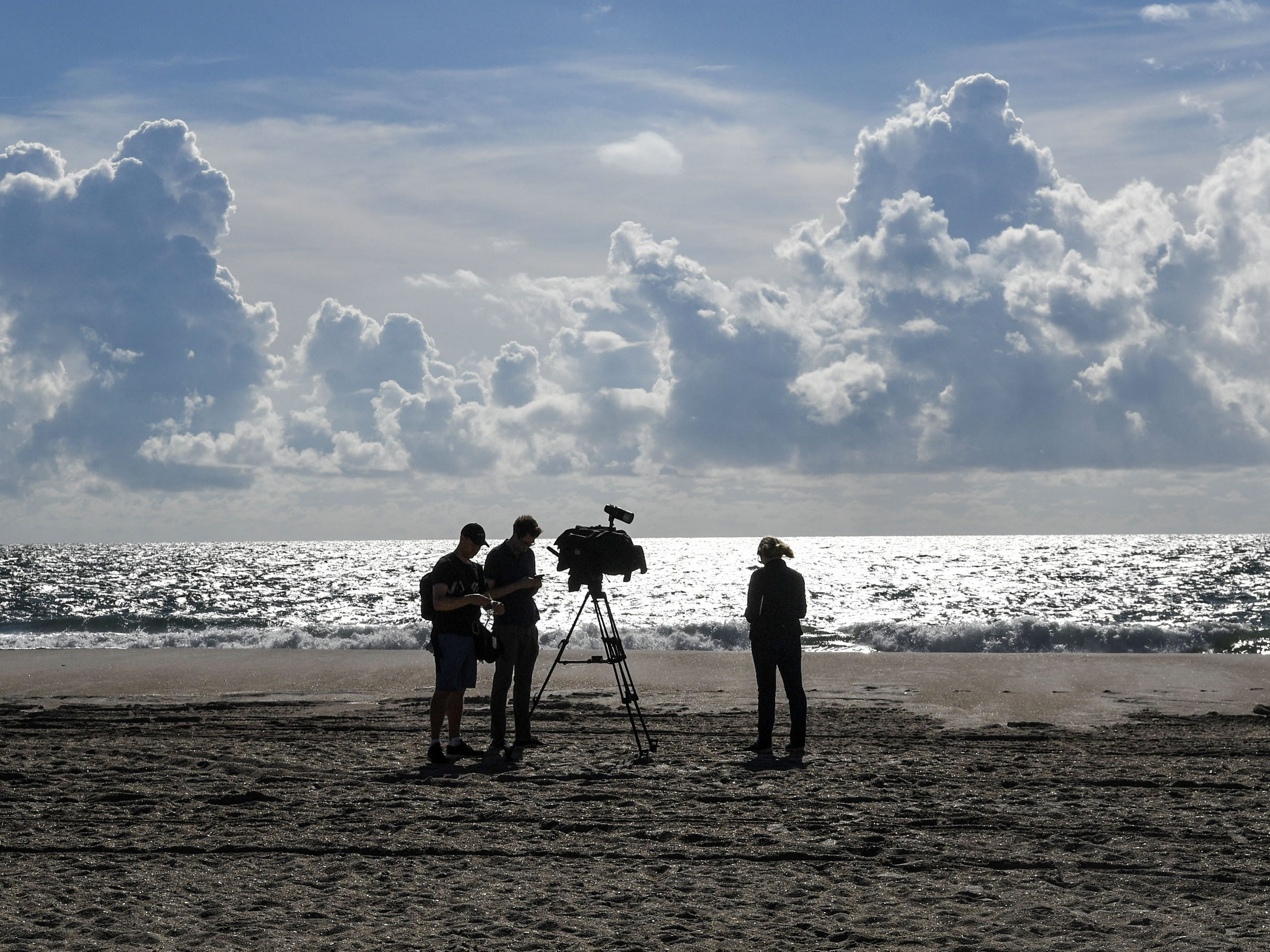 A news crew pauses between segments at Wrightsville Beach in Wilmington N.C. on Sept. 12, 2018.