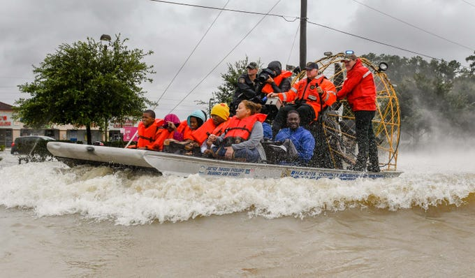 Volunteers and first responders work together to rescue residents from rising flood waters following Hurricane Harvey in Houston, Aug. 29, 2017.