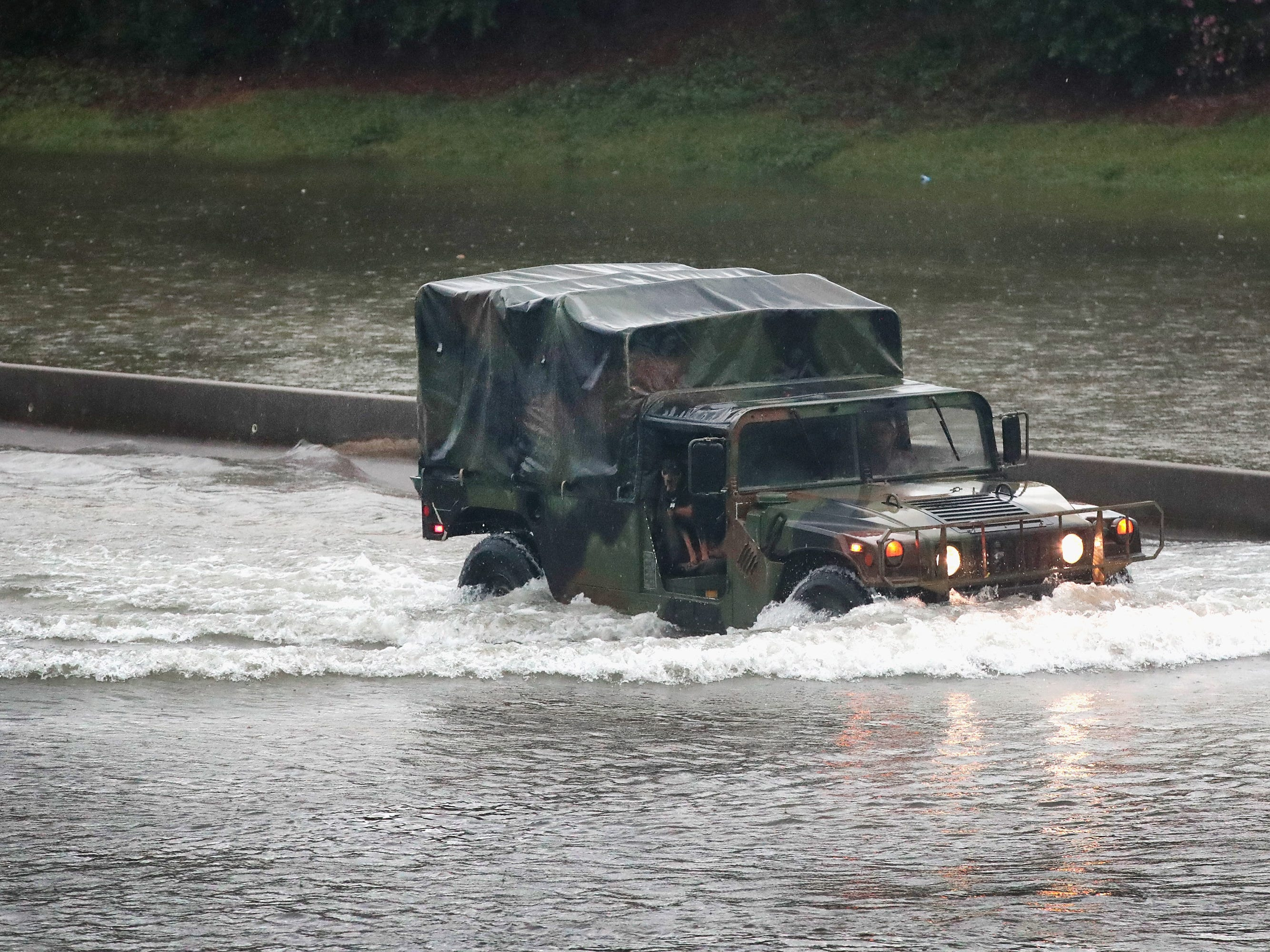 A military truck navigates along Interstate 10 which has been inundated with flooding from Hurricane Harvey on Aug. 27, 2017 in Houston, Texas.